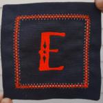 image of black coaster with E